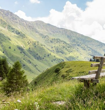 wooden bench in front of amazing view on valley and mountains